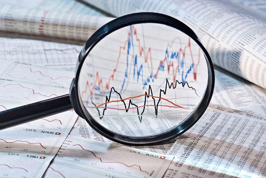 Lupe zeigt verschiedene Aktienkurse.