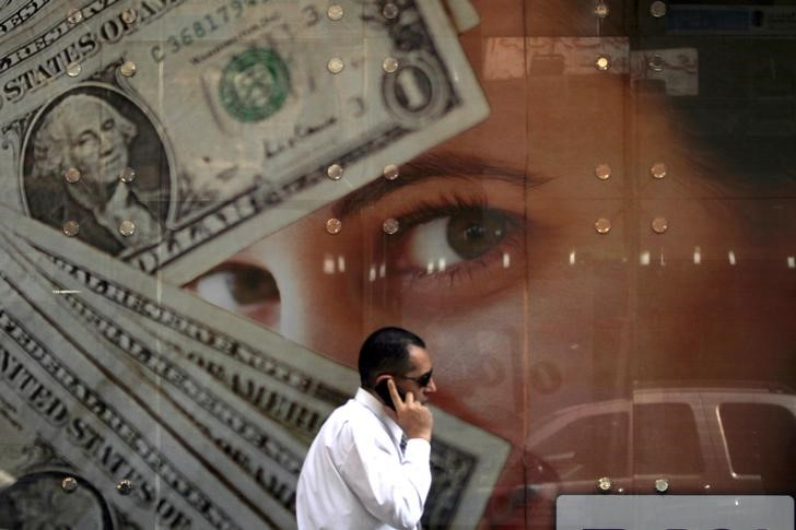 A man talks on his mobile phone as he walks past an exchange bureau advertisement showing images of the U.S dollar, in Cairo March 10, 2014. REUTERS/Amr Abdallah Dalsh